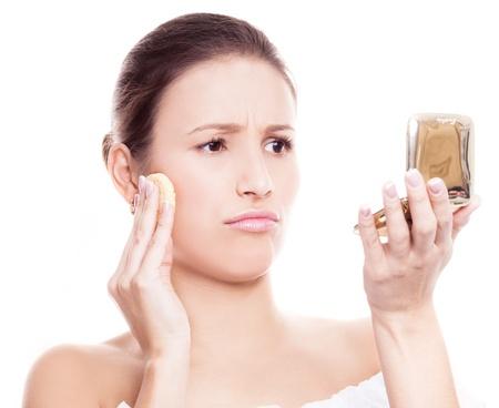 白い背景に対して隔離される化粧を適用する不満の女性の肖像画