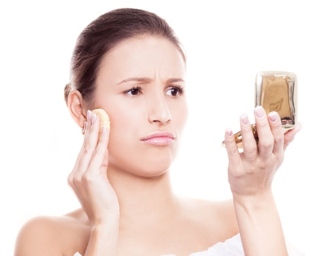 portrait of a displeased woman applying makeup, isolated against white background photo