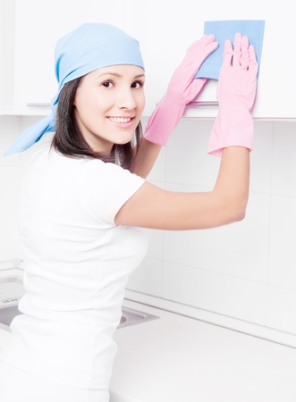 wipe: beautiful young housewife cleaning the furniture in the kitchen