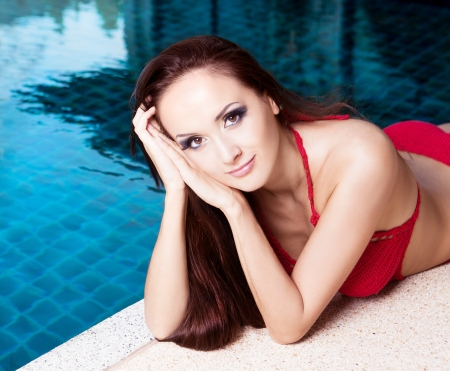 beautiful young brunette woman relaxing by the swimming pool  photo