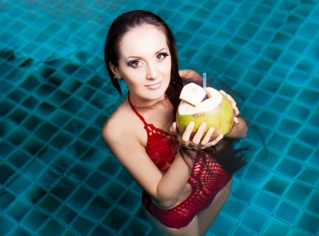 beautiful young brunette woman relaxing in the swimming pool and drinking coconut milk photo