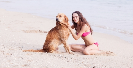 beautiful young woman with a dog on the beach photo