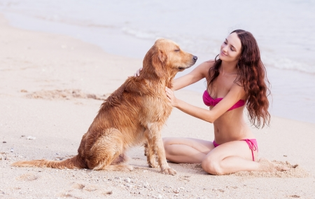 huge: beautiful young woman with a dog on the beach Stock Photo
