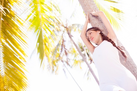 outsides: beautiful young woman standing near the palm tree