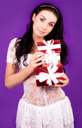 ger: beautiful young woman with a lot of gifts in her hands, isolated on purple studio background