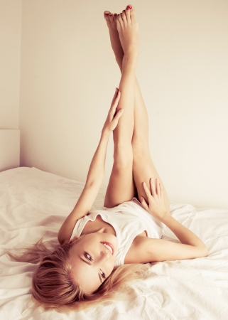beautiful young woman on the white linen in bed at home  photo