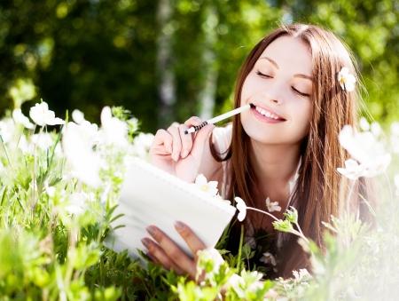 mooie jonge brunette vrouw het schrijven in haar dagboek op de weide met witte bloemen