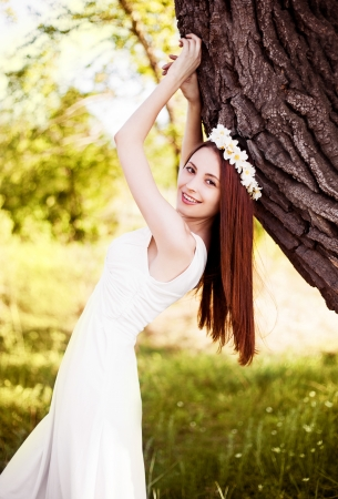 outsides: beautiful young brunette woman standing near th big tree on a warm summer day