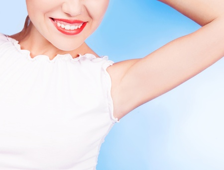 underarms: beautiful young woman showing underarms, on blue studio background Stock Photo
