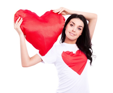 smiling young  woman wearing a  shirt with a big red heart and holding a heart-shaped pillow, isolated against white background photo