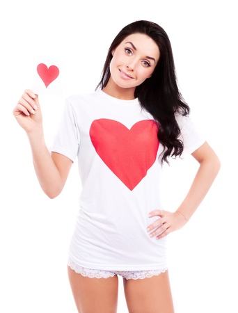 smiling young  woman wearing a shirt with a big red heart and holding a Valentine card, isolated against white background photo