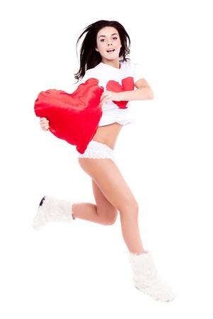 happy jumping young  woman wearing a shirt with a big red heart and holding a heart-shaped pillow, isolated against white background photo