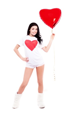 smiling young  woman wearing a  shirt with a big red heart and holding a heart-shaped balloon, isolated against white background photo
