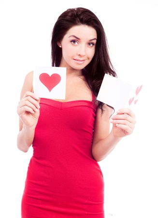 smiling young woman wearing a red dress and holding Valentine cards, isolated against white background photo