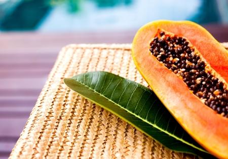 完熟パパイヤとスイミング プールのそばの枝編み細工品椅子に熱帯樹の葉