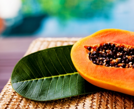 papaya tree: juicy papaya and a leaf of a tropical tree on the wicker chair near the swimming pool