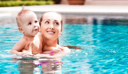 Schöne junge Brünette Frau mit ihrem 1 Jahr altes Baby Entspannung im Schwimmbad Standard-Bild - 17539883