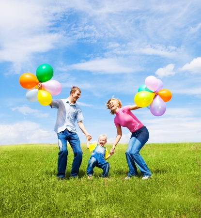 happy family with balloons  jumping outdoor on a warm summer day Stock Photo - 17646460