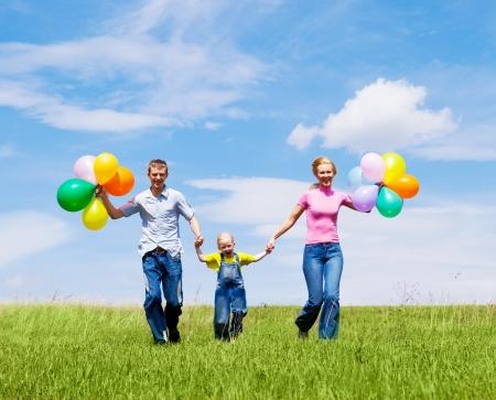 boldog család léggömbökkel futó kültéri egy meleg nyári napon