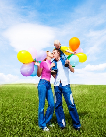 happy young family with balloons outdoor on a warm summer day, against blue sky photo