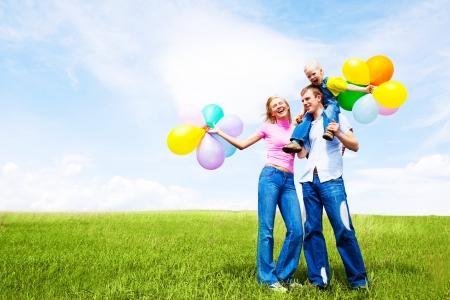風船の暖かい夏の日に屋外で幸せな家族