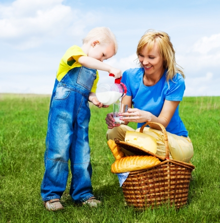 happy young  woman and her son having a picnic outdoor on a summer day photo