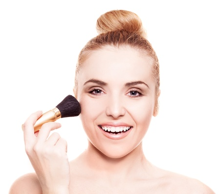 makeup brush: portrait of a beautiful woman applying makeup with a brush, isolated against white background