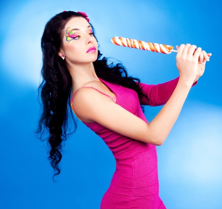 girl licking: pretty young brunette woman with a lollipop, isolated against blue background