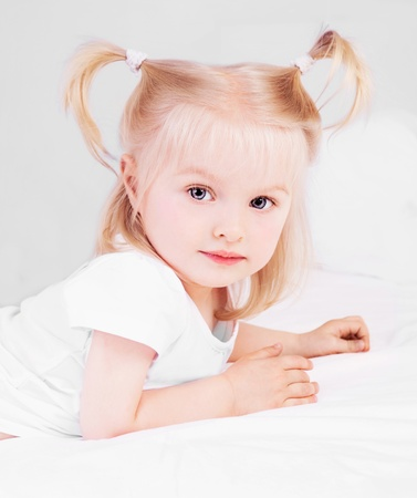two year old blond girl in bed at home photo