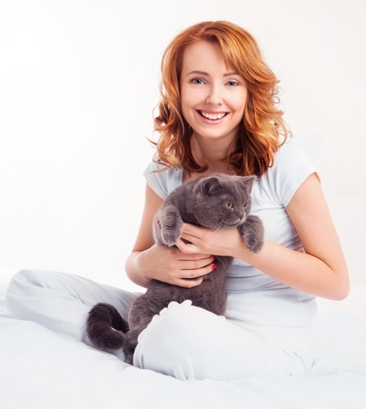 beautiful young woman with a cat in bed at home photo