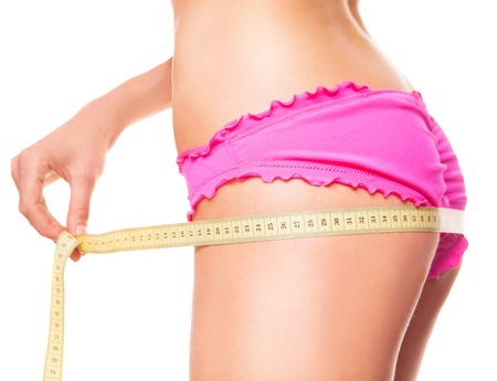 loose weight: slim woman measuring her hips with a measuring tape, isolated against white background Stock Photo