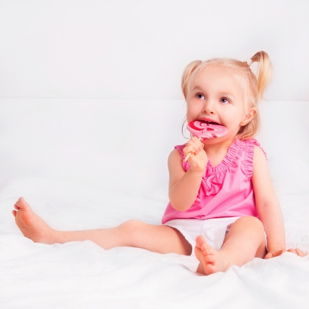 two year old: two year old blond girl eating a candy in bed at home Stock Photo