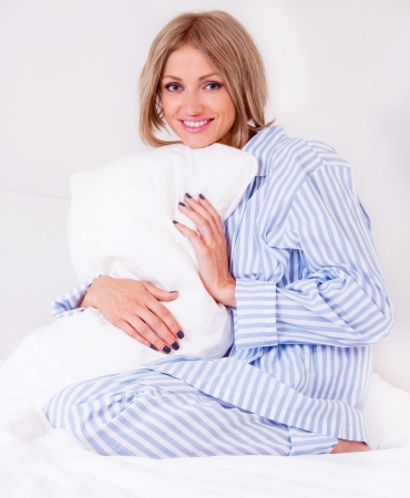 beautiful young woman wearing pajamas in bed at home photo