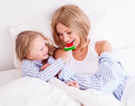 happy young mother with her daughter eating a candy in bed at home (focus on the child) photo
