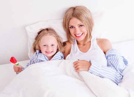 happy young mother with her daughter eating a candy in bed at home  photo
