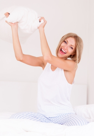 Pillow fight: pillow fight, beautiful young woman throwing a pillow at us in bed at home