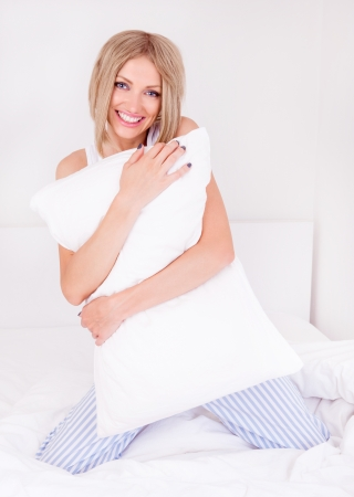 beautiful young woman wearing pajamas holding a pillow  in bed at home photo