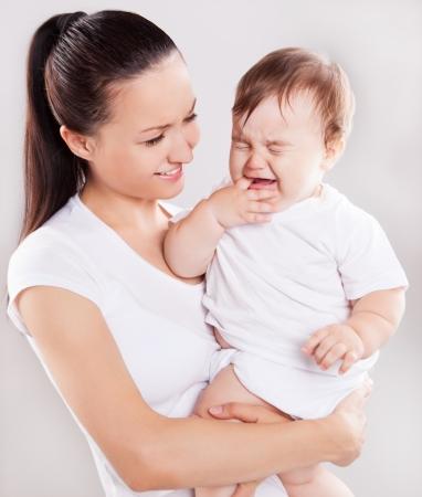 gyönyörű, fiatal anya kezében egy síró baba, fény ellen stúdió háttere Stock fotó