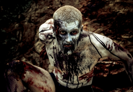 male killer: young man with a zombie body painting, covered with blood on the beach against a cliff