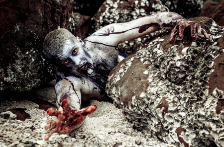 malevolent: young man with a zombie body painting, covered with blood on the beach against a cliff (halloween topic)