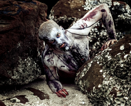 ghoulish: young man with a zombie body painting, covered with blood on the beach against a cliff (halloween topic)