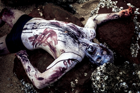 body painting: young man with a zombie body painting, covered with blood on the beach  (halloween topic)
