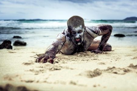 fiatal férfi egy zombi testfestés, vér borítja a strandon (halloween téma)