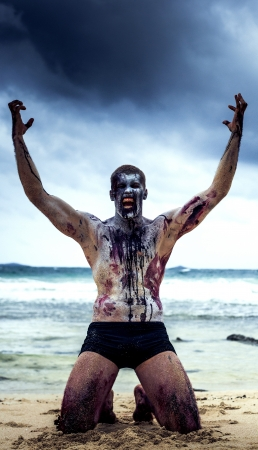 malevolent: young man with a zombie body painting, covered with blood, screaming on the beach  (halloween topic)