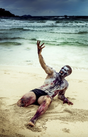 young man with a zombie body painting,without one leg, covered with blood, screaming on the beach  (halloween topic) photo