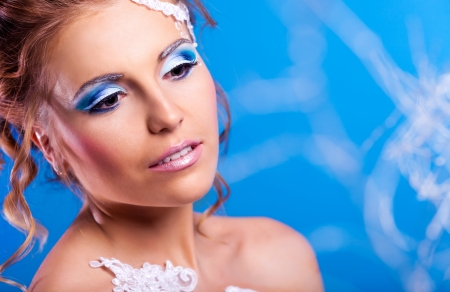 beautiful young woman with creative blue makeup, against blue studio background, winter topic photo