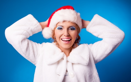 happy young woman wearing a Santa's hat, against blue studio background (Christmas topic) photo