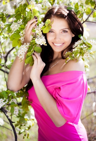 outsides: beautiful brunette woman in the park standing near the apple tree on a warm summer day