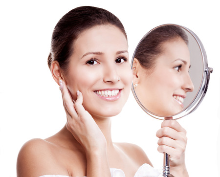 portrait of a happy beautiful woman looking into the mirror, isolated against white background photo