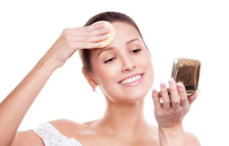 portrait of a happy beautiful woman looking into the mirror and applying cosmetics, isolated against white background photo